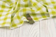 在一张白色木桌上的绿色布料 免版税库存图片