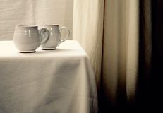 在一张白色桌上的两个白色茶杯反对白色背景 免版税库存照片