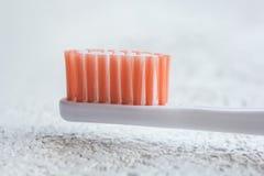 在一张白色桌上的新的橙色发怒的牙刷顶头特写镜头 个人卫生在被弄脏的背景的面孔特写镜头主题  库存图片