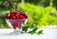 在一张白色桌上的水多的红色cornelias 季节性莓果 库存图片
