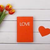 在一张白色桌上的红色书爱 开花郁金香 免版税库存照片