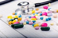 在一张白色桌上的药房背景 在白色木背景的听诊器 复制文本的空间 在一白色backgrou的片剂 库存照片