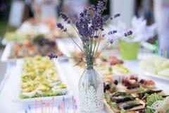 在一张白色桌开胃快餐和一个美丽的玻璃花瓶wi 免版税库存照片