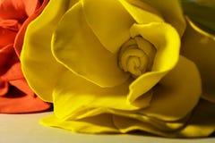 在一张白色纸片的一朵人为黄色和红色玫瑰,点燃由台灯 免版税库存照片