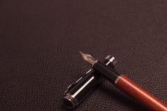 在一张皮革书桌上的钢笔 图库摄影