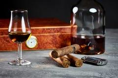 在一张石桌与打火机和一个木雪茄盒上的三古巴雪茄有玻璃和一个瓶的威士忌酒 库存照片