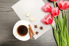 在一张空白的纸片的桃红色郁金香、杯子咖啡和香料,黑木背景 顶视图 库存照片