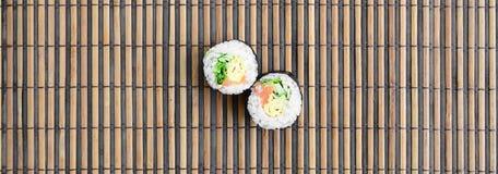 在一张竹秸杆serwing的席子寿司卷谎言 亚洲食物炒饭传统蔬菜 顶视图 与拷贝空间的平的被放置的简单派射击 库存照片