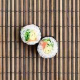 在一张竹秸杆serwing的席子寿司卷谎言 亚洲食物炒饭传统蔬菜 顶视图 与拷贝空间的平的被放置的简单派射击 免版税图库摄影