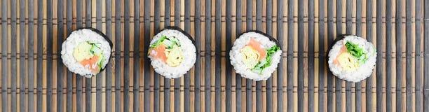 在一张竹秸杆serwing的席子寿司卷谎言 亚洲食物炒饭传统蔬菜 顶视图 与拷贝空间的平的被放置的简单派射击 免版税库存图片