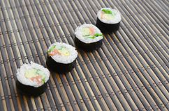 在一张竹秸杆serwing的席子寿司卷谎言 亚洲食物炒饭传统蔬菜 库存照片