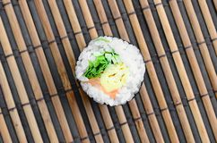 在一张竹秸杆serwing的席子的寿司卷谎言 亚洲食物炒饭传统蔬菜 顶视图 与拷贝空间的平的被放置的简单派射击 免版税库存图片