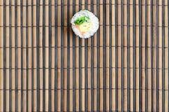 在一张竹秸杆serwing的席子的寿司卷谎言 亚洲食物炒饭传统蔬菜 顶视图 与拷贝空间的平的被放置的简单派射击 库存图片