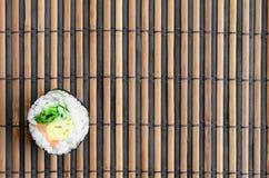 在一张竹秸杆serwing的席子的寿司卷谎言 亚洲食物炒饭传统蔬菜 顶视图 与拷贝空间的平的被放置的简单派射击 免版税图库摄影