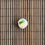 在一张竹秸杆serwing的席子的寿司卷谎言 亚洲食物炒饭传统蔬菜 顶视图 与拷贝空间的平的被放置的简单派射击 库存照片