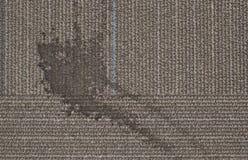 在一张简单的地毯的一个杂乱液体污点 库存图片