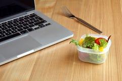 在一张繁忙的办公室工作者的书桌的沙拉 免版税库存照片