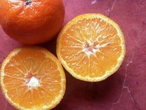 在一张红色桌上的新鲜的蜜桔 免版税图库摄影