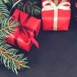 在一张红色纸包裹的云杉的分支和礼物顶视图与 免版税库存照片