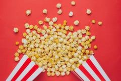 在一张红色背景顶视图的玉米花在戏院 库存照片