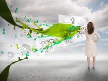 在一张纸的创造性的女实业家图画在油漆飞溅旁边 库存照片
