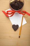 在一张纸的巧克力曲奇饼心脏与铅笔的 库存图片