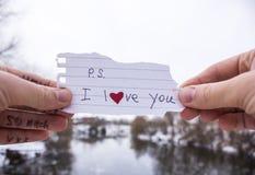 在一张纸的题字关于在人和女孩的胳膊的爱 免版税图库摄影