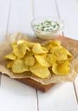 在一张羊皮纸的土豆片用在一张白色桌上的调味汁 免版税图库摄影