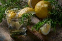 在一张老木桌上的蓝色杜松子酒、补品和柠檬切片 库存图片