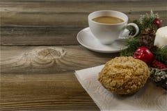 在一张老桌上的咖啡杯与圣诞节花圈和松饼 免版税库存照片