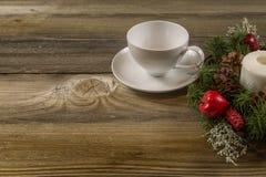 在一张老桌上的咖啡杯与圣诞节花圈 库存照片