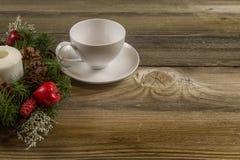 在一张老桌上的咖啡杯与圣诞节花圈 免版税库存照片