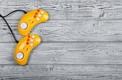 在一张老灰色木背景桌上的电子游戏控制台GamePad 黄色减速火箭的GamePad 复制空间 免版税库存照片
