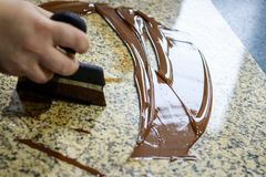 在一张花岗岩桌上的薄层应用的液体缓和巧克力它的冷却 免版税图库摄影