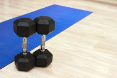 在一张蓝色地毯的哑铃在健身房 库存图片