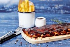 在一张蓝色木桌上的烤肉肋骨 免版税库存照片