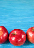 在一张蓝色木桌上的红色苹果 免版税库存照片