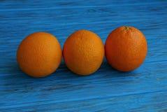 在一张蓝色桌上的三个大成熟桔子 库存图片