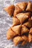 在一张被撒粉于的桌上的印地安samosa酥皮点心 垂直的顶视图 图库摄影