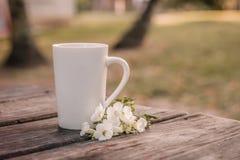 在一张被风化的桌上的一个加奶咖啡杯子 库存照片