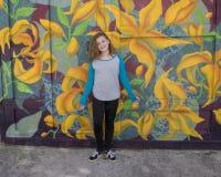 在一张车库门壁画前面的熟悉内情的11岁的女孩在南费城 图库摄影