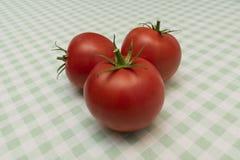 在一张轻的方格的桌布的三个成熟红色蕃茄 免版税图库摄影