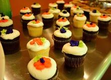 在一张银色桌上的五颜六色的杯形蛋糕用曲奇饼 库存图片