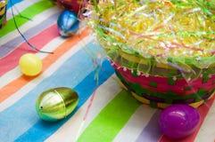 在一张镶边桌布的五颜六色的复活节彩蛋在一个明亮的被编织的篮子附近 库存图片