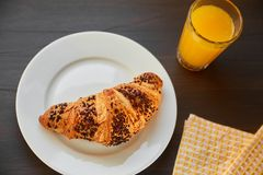 在一张陶瓷板材和洗碗布的新鲜的新月形面包与一个杯子橙汁 在一张黑暗的木桌上的新近地被烘烤的新月形面包 库存图片