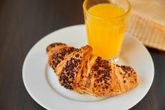 在一张陶瓷板材和洗碗布的新鲜的新月形面包与一个杯子橙汁 在一张黑暗的木桌上的新近地被烘烤的新月形面包 免版税库存照片