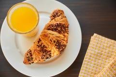 在一张陶瓷板材和洗碗布的新鲜的新月形面包与一个杯子橙汁 在一张黑暗的木桌上的新近地被烘烤的新月形面包 免版税库存图片