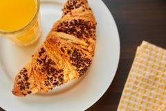 在一张陶瓷板材和洗碗布的新鲜的新月形面包与一个杯子橙汁 在一张黑暗的木桌上的新近地被烘烤的新月形面包 免版税图库摄影