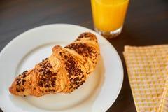 在一张陶瓷板材和洗碗布的新鲜的新月形面包与一个杯子橙汁 在一张黑暗的木桌上的新近地被烘烤的新月形面包 图库摄影