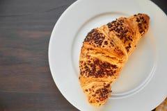 在一张陶瓷板材和洗碗布的新鲜的新月形面包 在一张黑暗的木桌上的新近地被烘烤的新月形面包 图库摄影